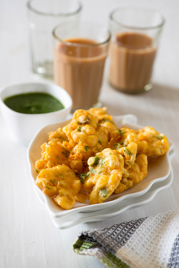 Corn Pakoda is a delicious teatime snack or Indian starter dish. Corn Pakora is an easy recipe in which deep-fried crisp corn fritters are made with chickpeas flour, sweet corn and regular Indian spices. As rainy season is about to arrive and we are already having few showers here and there. In India, we are conditioned to celebrate monsoon with Rainy day food like crisp hot pakoda. Corn pakoda makes excellent rainy day snack