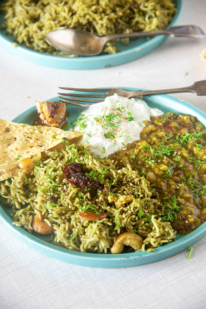 spinach rice served with whole moong dal and raita